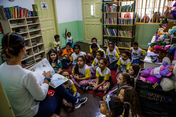 Um grupo de crianças sentado no chão acompanha a leitura de livro pela professora. Ela está sentada numa cadeira diante das crianças, dentro de uma sala de brinquedos