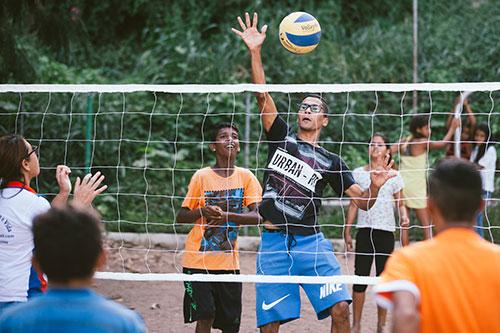 Num jogo de vôlei entre jovens, rapaz salta junto à rede para bloquear a passagem da bola