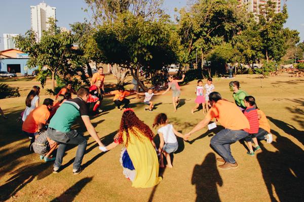 Num dia ensolarado em um parque, é feita uma roda com voluntários do Itaú-Unibanco e crianças durante ação voluntária