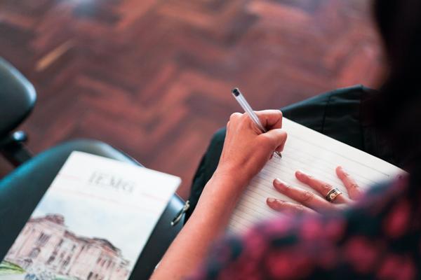 Pessoa escreve com caneta num caderno apoiado em suas pernas