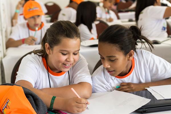 Duas garotas sentadas numa carteira escolar fazem atividades escolares juntas. Uma delas escreve a lápis num caderno