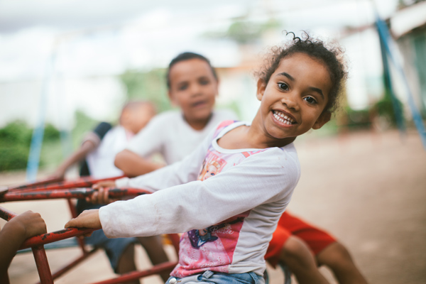 Crianças brincam num gira-gira, enquanto uma menina sorri diretamente para a câmera