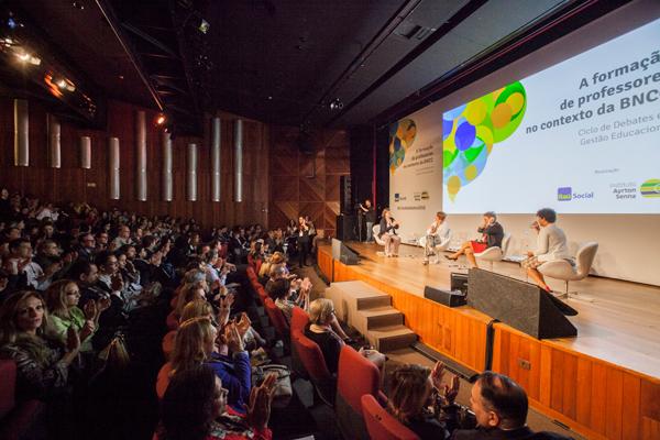 Foto de parte do palco, com palestrantes sentadas, e auditório cheio, durante o Seminário Ciclo de Debates 2018