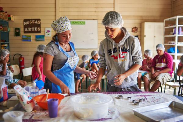 Jovens cozinham dentro de uma sala adaptada com equipamentos e utensílios de cozinha
