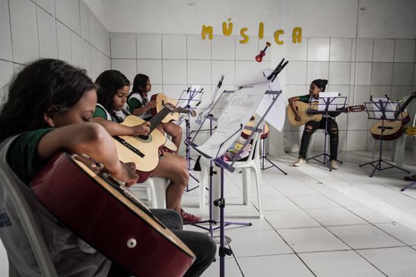 Grupo de meninas, dispostas em círculo, toca violão dentro de uma sala