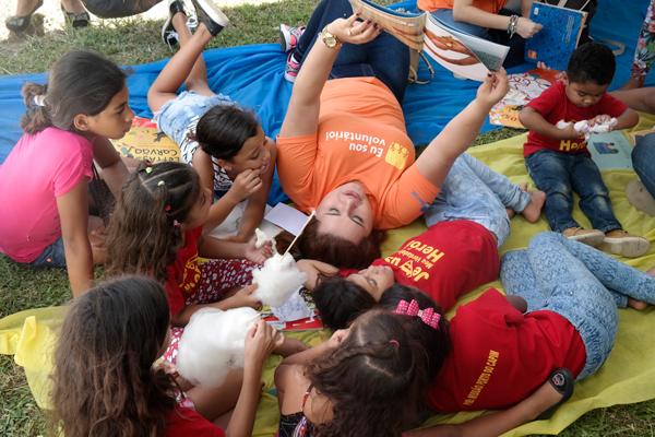 Colaboradora do Itaú-Unibanco, vestindo camiseta na cor laranja, lê livro para grupo de crianças durante ação voluntária