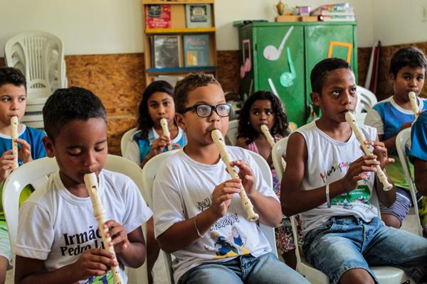 Grupo de crianças, sentado, toca flauta dentro de uma sala