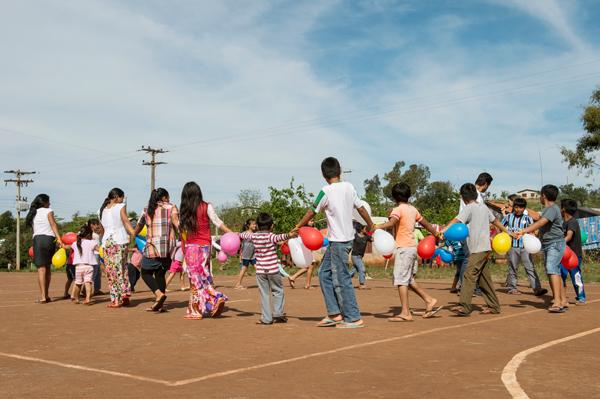 Adultos, crianças e jovens de uma tribo indígena fazem um círculo, de mãos dadas, durante atividade de projeto social