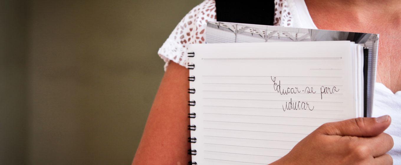 """Menina segurando um caderno espiral junto ao corpo, aberto numa folha em que está escrito a mão """"Educar-se para educar"""""""