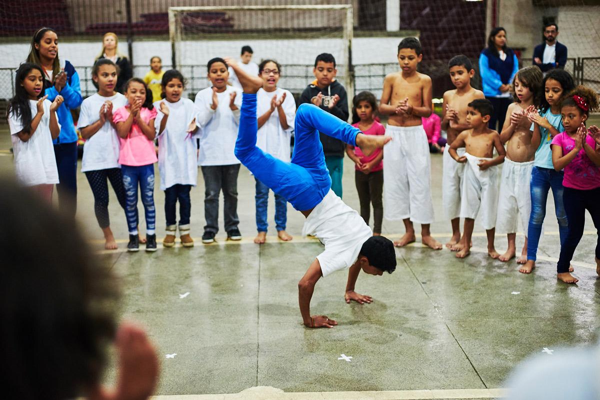 Numa roda de capoeira, crianças dispostas em círculo observam um jovem, no centro, fazendo posições desse esporte