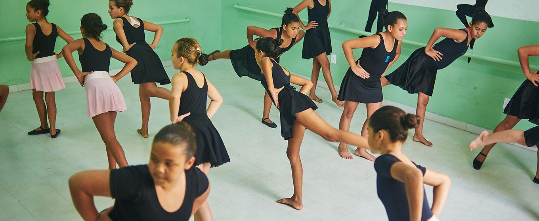 Grupo de meninas participa de aula balé numa sala