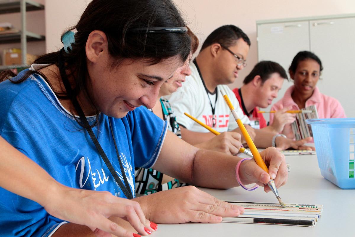 Grupo de adultos pinta tubos feitos com papel de jornal durante aula